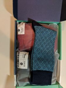 The opened shipping box has three items inside: a pair of blue and green socks with a design on them and two lounge shorts in plastic bags, one red and the other black.