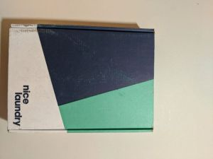 A rectangular shipping box with Nice Laundry in the bottom-right corner. There are three colors on the box: blue, light green, and white.