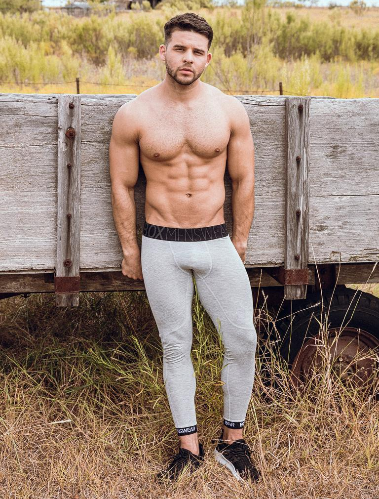 Fitness model Josh Riquelme stands in front of a farm trailer in grass while wearing Box Menswear lounge leggings.