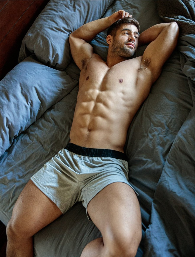 A muscular Dan Tai relaxes in bed in sunlight while wearing Box Menswear lounge shorts.