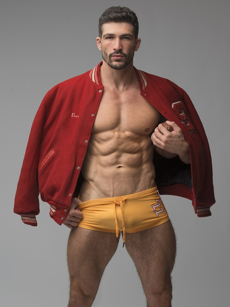 Muscular model Dominic Calvani poses with a football, a red varsity jacket and yellow trunk shorts.