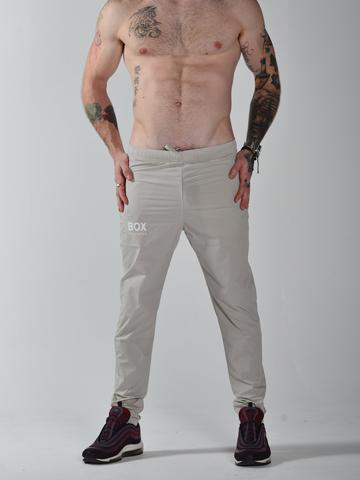 Male model with body art wears stone (beige) Box Menswear performance fitted joggers.