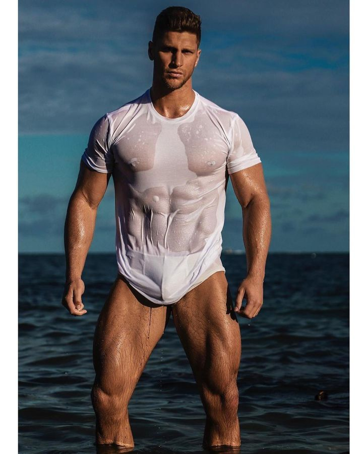 Muscular fitness model from Canada, Kyle Hynick, stands in Atlantic Ocean in Miami in white t-shirt and briefs.