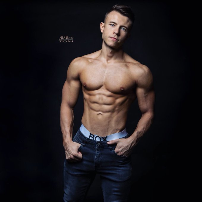 Model Tom Seed poses with flexed abdominal muscles wearing jeans in a photo by Alex Botic.