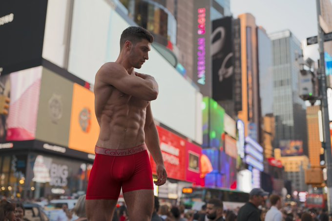 Fitness model Kyle Hynick from Canada poses in front of an electronic billboard in public for a photoshoot with Photographer Jade Young.