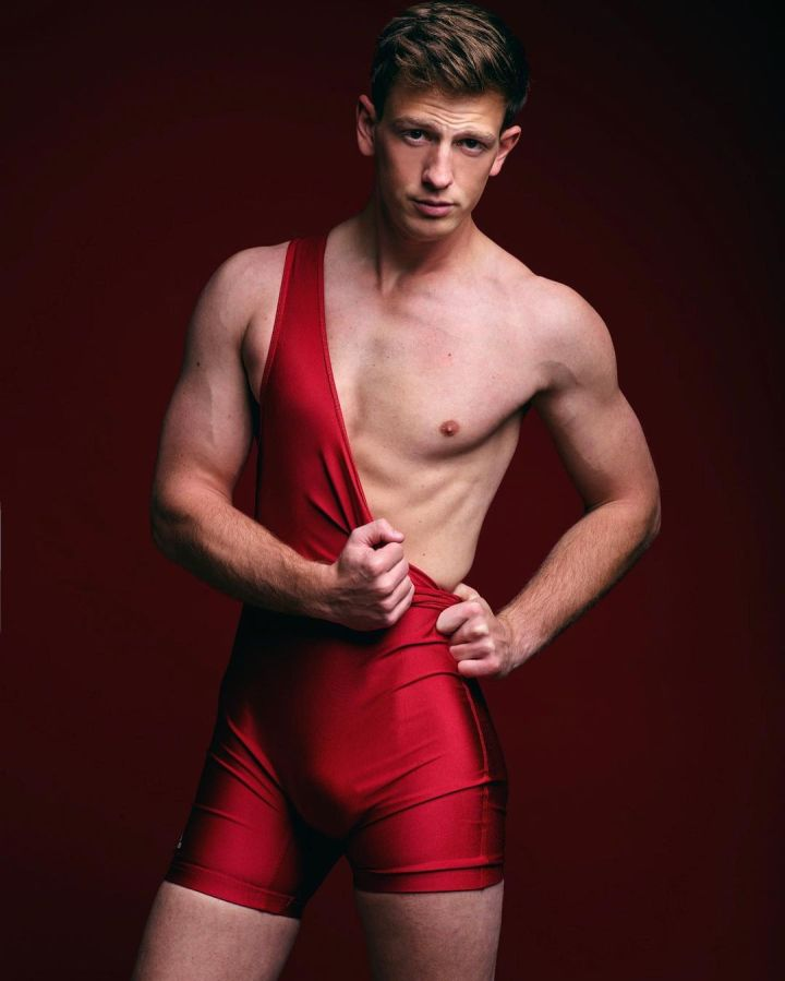 Muscular model Buckahroo in a red wrestling singlet.