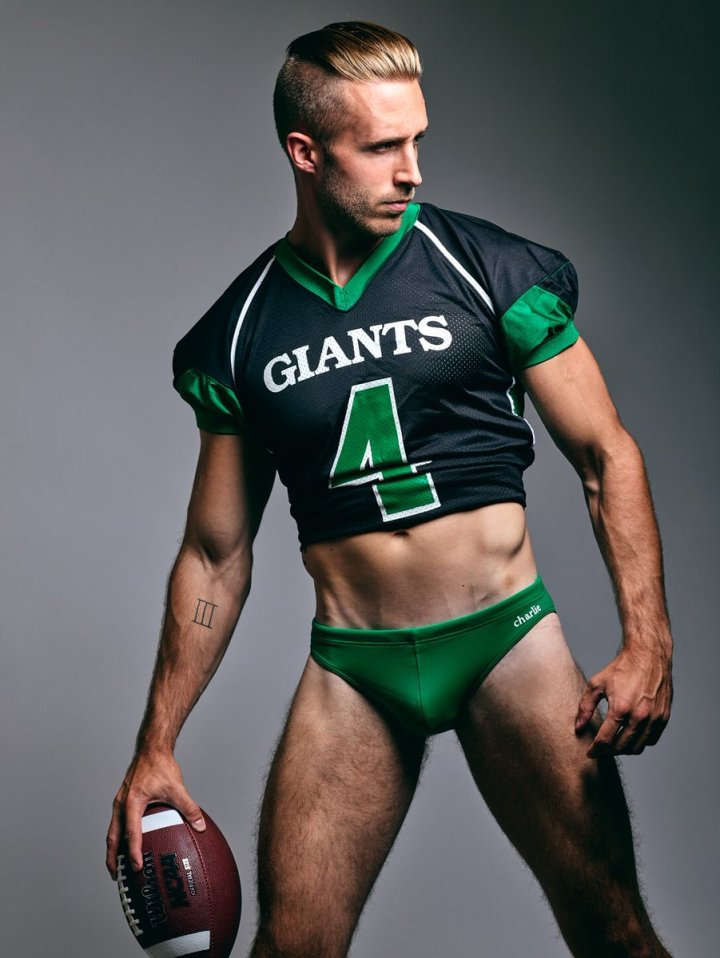 Model, actor, and Texas-based photographer Dillion Lalor posed in a green and black American football jersey and holds a football  in his left hand while looking at something on the right side of the image. Dillion wears green swim briefs from the charlie brand.