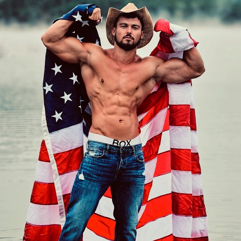 "UK reality show actor Josh Watson stands for a photo bt Carlos ""Trey"" Salazar. Josh stands in the center of the frame with two flexed biceps while holding a United States flag. Josh wears denim jeans."